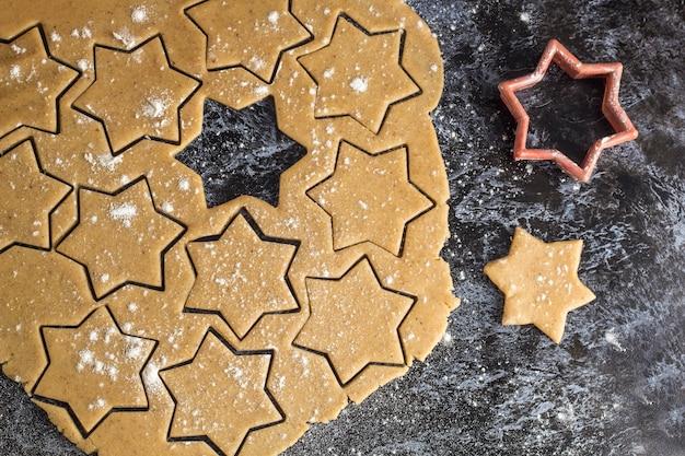 Massa de pão caseiro de natal cru, desenrolada na mesa escura Foto Premium