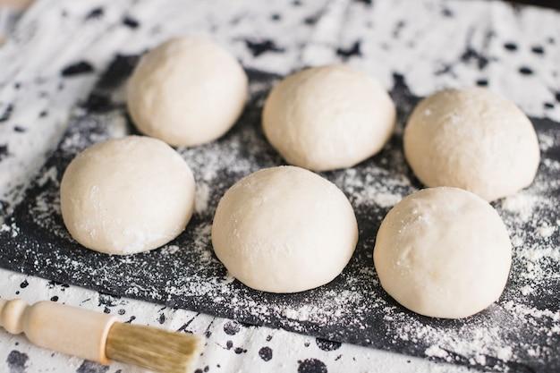 Massa de pão na ardósia com farinha e escova Foto gratuita