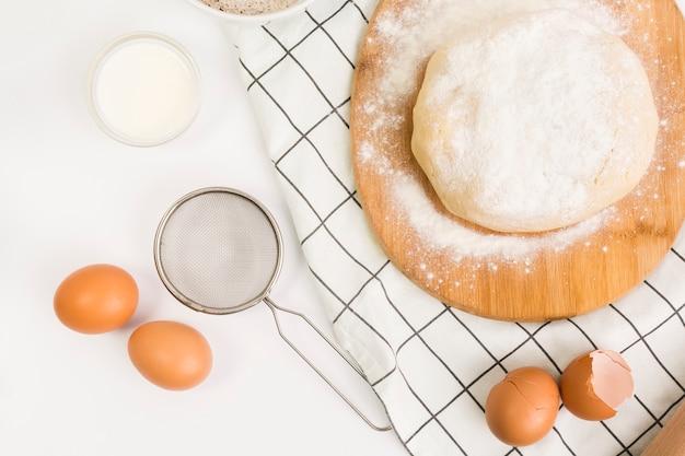 Massa de pastelaria unbaked e ingrediente cru sobre a superfície branca Foto gratuita