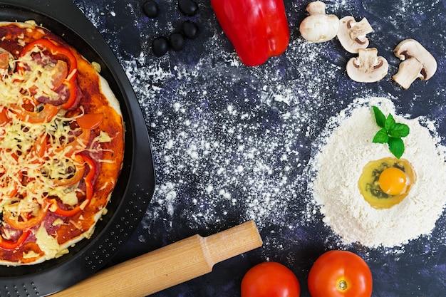 Massa de pizza crua com ingredientes e especiarias no escuro Foto Premium
