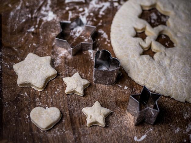 Massa do bolinho da padaria com molde do corte na mesa de cozinha. Foto Premium