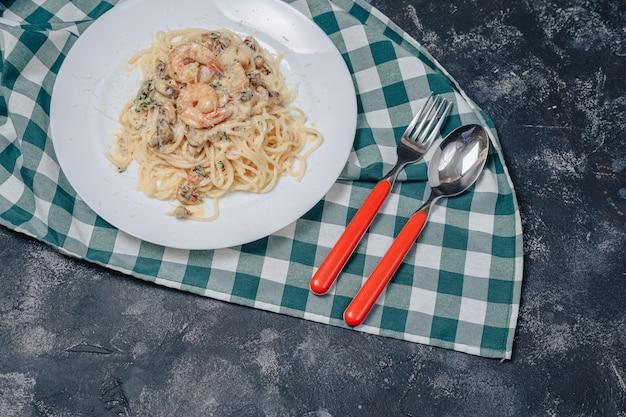 Massa italiana com frutos do mar e camarão rei, espaguete com molho Foto gratuita