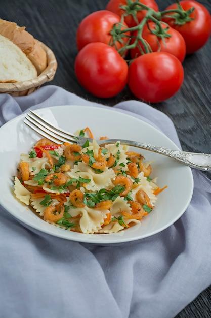 Massa italiana em um molho com camarões em um prato, vista superior. de madeira escura. . Foto Premium
