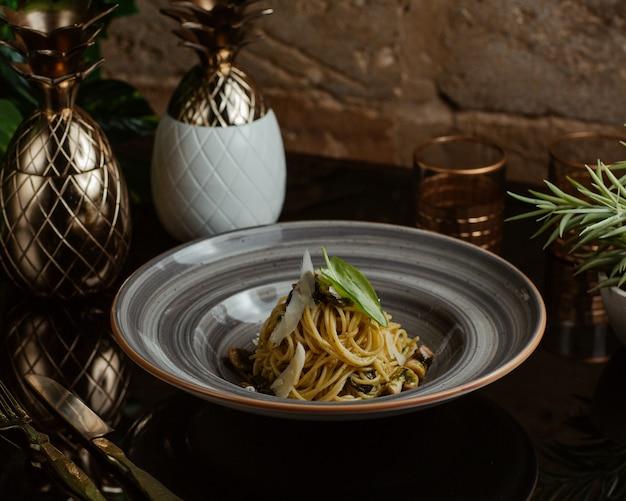Massa italiana tradicional com cogumelos, fatias de parmesão e folhas de orégano em uma tigela de granito Foto gratuita