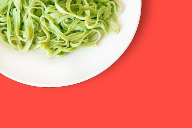 Massa verde em um prato branco isolado em um coral vivo Foto Premium
