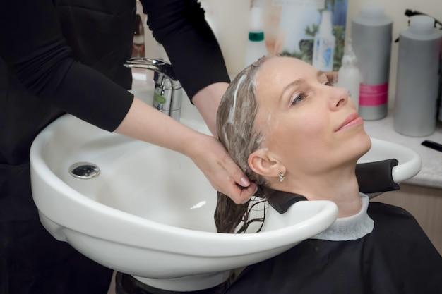 Massageando couro cabeludo e cabelo com shampoo. lavagem de cabelos no salão. Foto Premium
