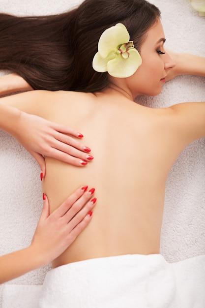 Massagem de pedra spa. mulher bonita recebendo spa hot stones massage no salão de beleza spa. tratamentos de beleza ao ar livre. natureza Foto Premium