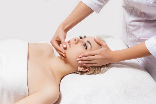 Massagem de rosto. close-up de uma jovem mulher recebendo massagem spa em um salão de beleza e spa por esteticista. cuidados com a pele e corpo do spa. cuidados com o rosto de beleza. cosmetologia. Foto Premium