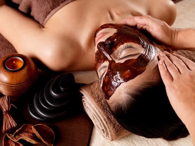 Massagem de spa para jovem com máscara facial no rosto - dentro de casa Foto gratuita
