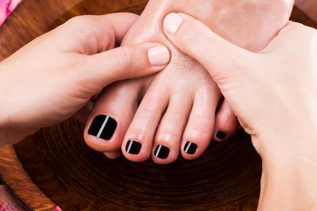 Massagem do pé feminino em salão de spa - conceito de tratamento de beleza Foto gratuita