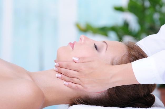 Massagem facial feminina no salão de beleza - close-up do perfil Foto gratuita