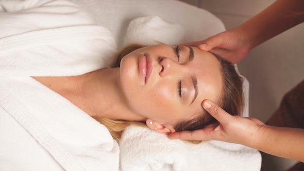 Massagem na cabeça e no rosto de uma mulher bonita em close-up, uma mulher cuidando do rosto Foto Premium