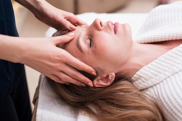 Massagem na cabeça na mulher relaxada no spa Foto gratuita