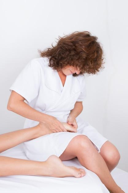 Massagem nos pés feita por mulher encaracolada Foto Premium