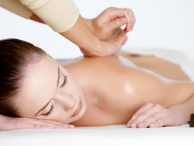 Massagem relaxante nas costas para jovem mulher bonita Foto gratuita