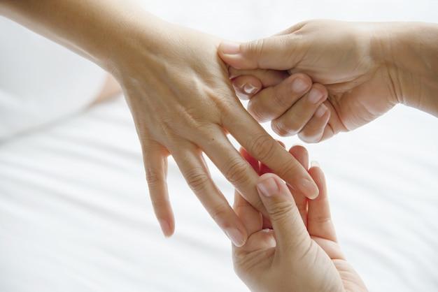 Massagem spa mão sobre cama branca limpa Foto gratuita