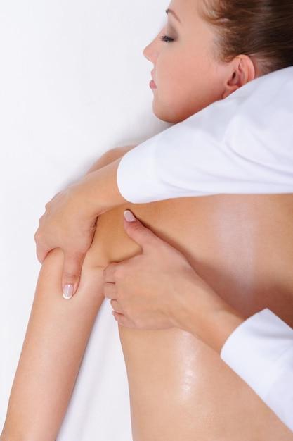 Massagem terapêutica para costas e ombros femininos - deitada na cama Foto gratuita