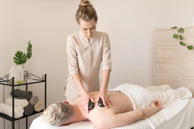Massagista de tiro médio com pedras Foto gratuita