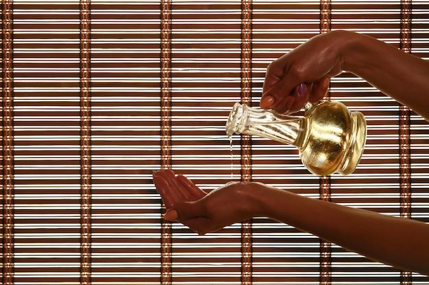 Massagista derrama óleo de fragrância na palma da mão Foto Premium