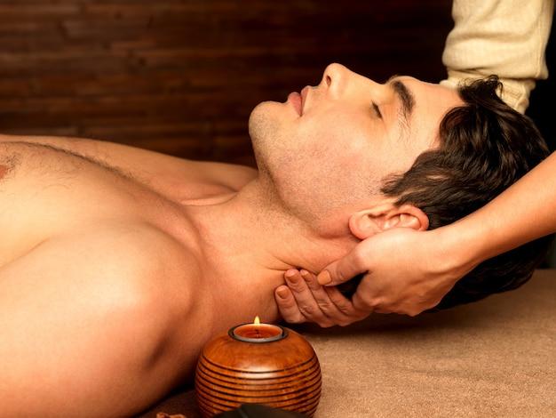 Massagista fazendo massagem no pescoço do homem no salão spa. Foto gratuita