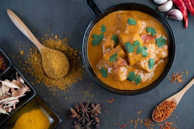 Massaman curry em uma frigideira com especiarias no chão de cimento Foto gratuita