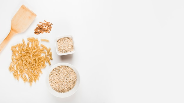 Massas alimentícias não cozidas; arroz e canela esmagada com espátula no fundo branco Foto gratuita