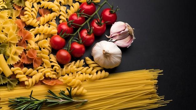 Massas e ingredientes para cozinhar em pano de fundo escuro Foto gratuita