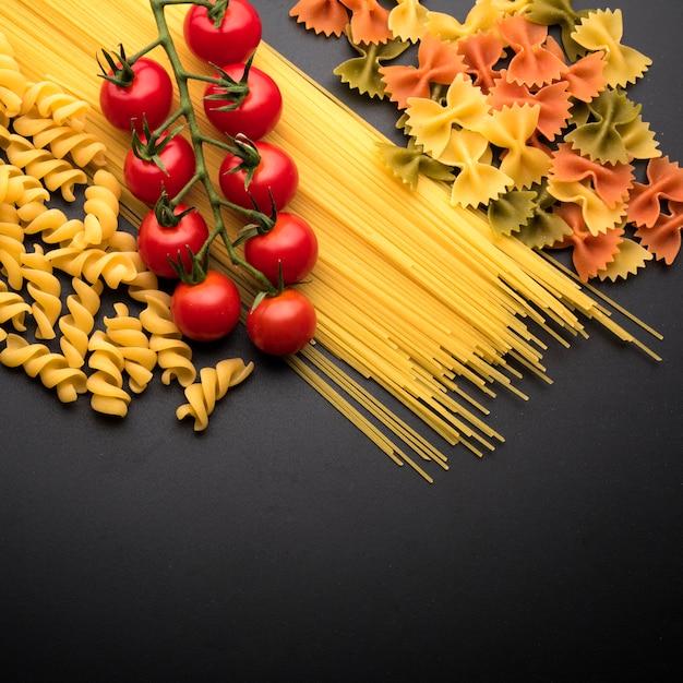 Massas italianas cozidas e tomates cereja sobre a bancada da cozinha Foto gratuita