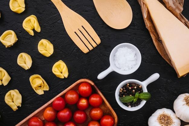 Massas recheadas e utensílios perto de ingredientes de cozinha Foto gratuita