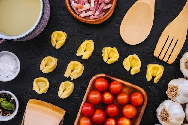 Massas recheadas em meio a ingredientes e utensílios de cozinha Foto gratuita
