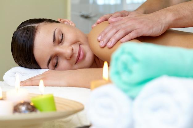Masseur que faz a massagem no corpo da mulher Foto gratuita