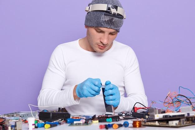 Master monta telefone e conserta-o com a substituição de nova bateria e tela Foto gratuita