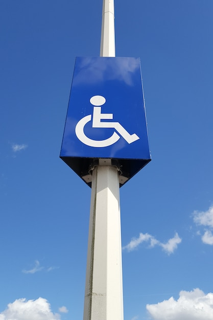 Mastro com sinalização rodoviária e vaga reservada a pessoas com deficiência Foto Premium