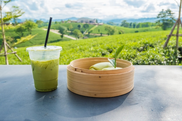 Matcha gelado chá verde em vidro de plástico transparente e mesa de pão cozido no vapor com fundo de plantação de chá Foto Premium