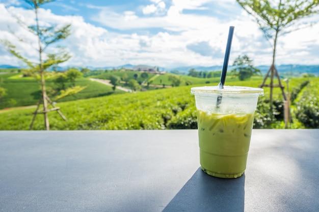 Matcha gelado chá verde em vidro plástico transparente na mesa com fundo de plantação de chá em choui fong Foto Premium
