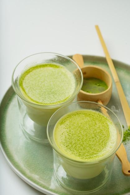 Matcha latte café alternativo saudável em uma bandeja de cerâmica decorada com pó matcha, colher de bambu chashaku e filtro. fechar-se Foto Premium