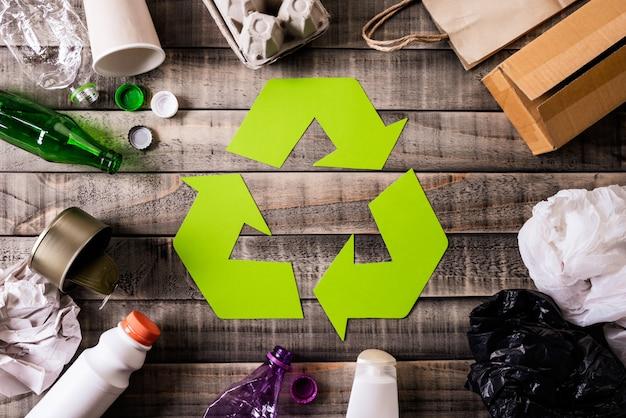 Materiais de lixo diferentes com símbolo de reciclagem no fundo da tabela Foto Premium