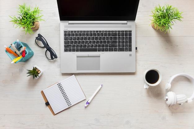 Material de escritório com laptop; fone de ouvido e xícara de café na mesa de madeira Foto gratuita
