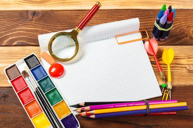 Material de escritório escolar em fundo de madeira Foto Premium