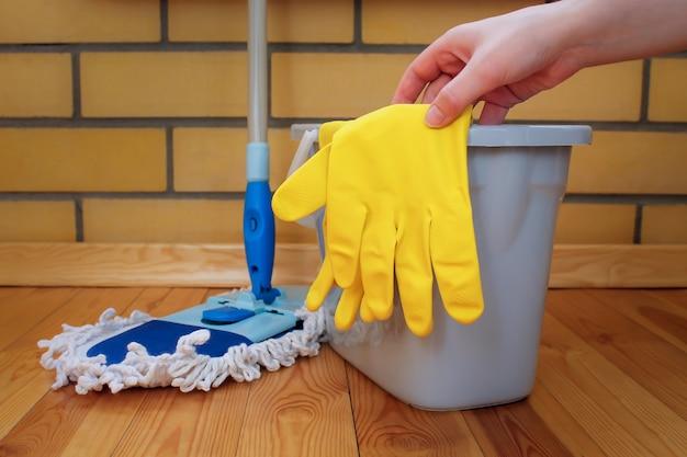 Material de limpeza. esfregão, balde de plástico e luvas de borracha, mão alcança a luva Foto Premium