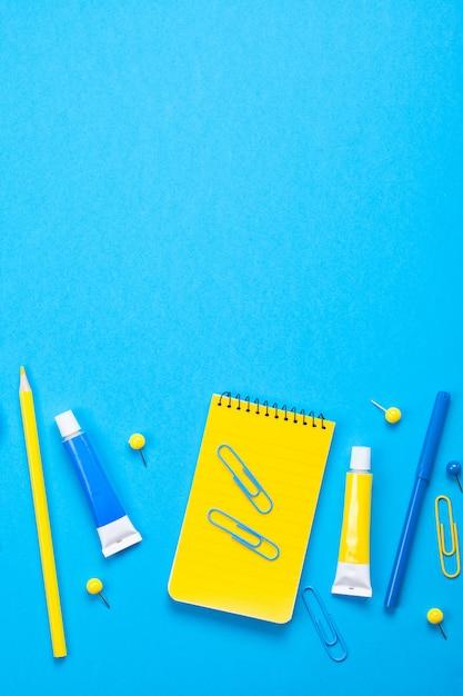 Material escolar amarelo sobre o fundo azul pastel. Foto Premium