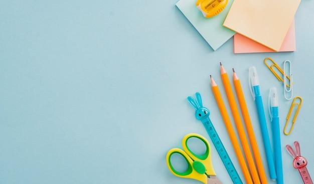 Material escolar artigos de papelaria em azul, volta ao conceito de escola, com espaço de cópia de texto, plano leigos Foto gratuita
