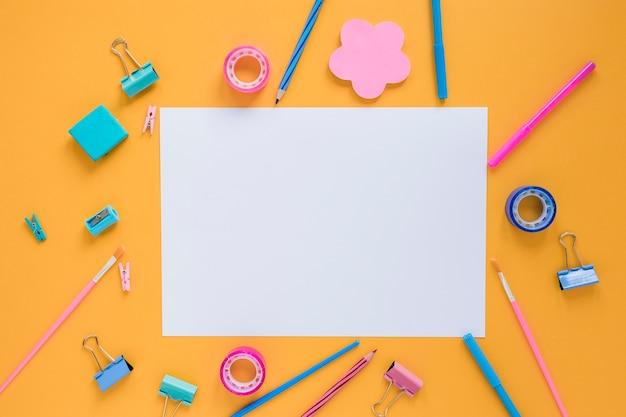 Material escolar colorido com papel em branco no centro Foto gratuita