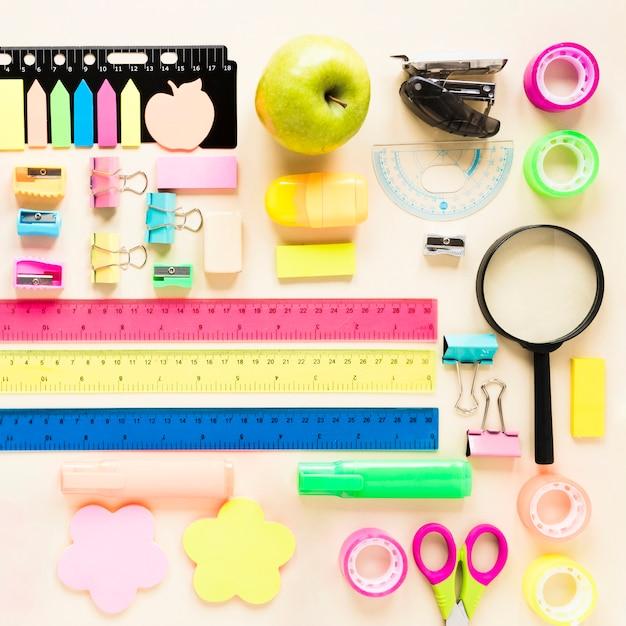 Material escolar colorido sobre fundo rosa claro Foto gratuita