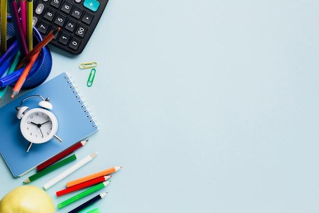 Material escolar e despertador organizado na mesa azul Foto gratuita