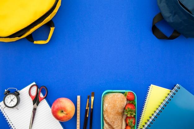 Material escolar e lancheira em fundo azul Foto gratuita