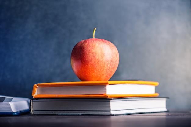 Material escolar em cima da mesa. livros e maçãs é uma coleção do aluno. Foto Premium