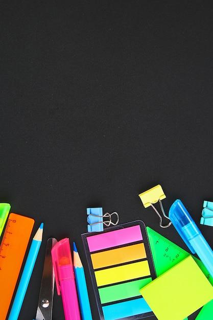 Material escolar em um fundo de quadro-negro Foto Premium