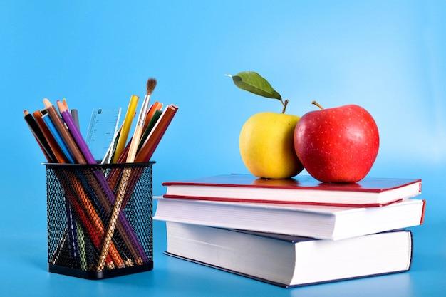 Material escolar lápis, canetas, régua, pincel, livros e maçã azul Foto Premium