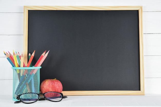 Material escolar na placa preta e branca de madeira Foto Premium